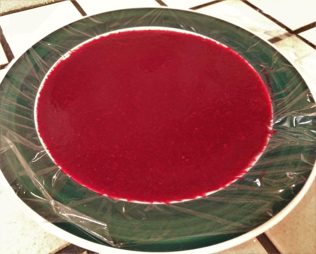 Himbeerrote Torten-Fruchteinlage in einem mit Frischhaltefolie ausgelegten Teller.